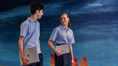 students holding laptops
