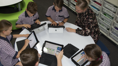 Children in a classroom working as a group on laptops with their teacher