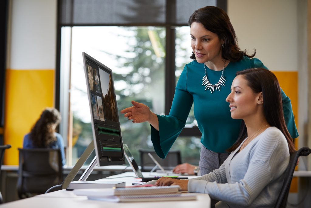 Female university staff member assisting a female student working on a Microsoft Surface Studio computer