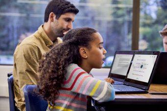 Girl sitting at desk with teacher using immersive reader on computer.