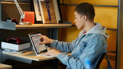 Male in bedroom on laptop working