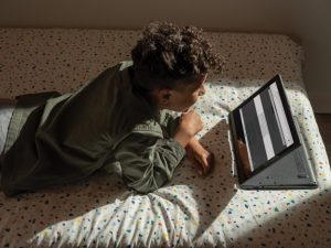 Boy laying on bed with device