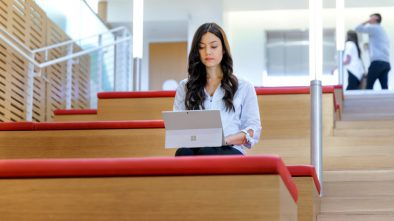 Female sitting in lecture hall with laptop