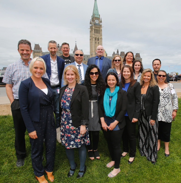 A group of teachers poses in front of the Canadian Parliament Buildings