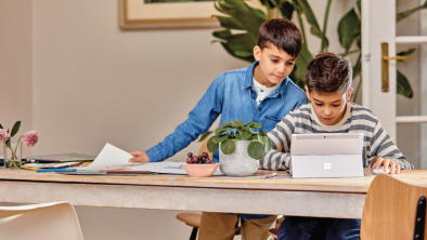 Two boys do school work on a laptop at a desk at home